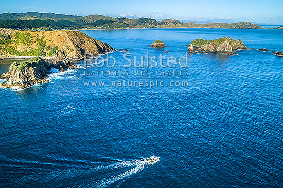 Fishing vessel passing Opito Point (left) and Rabbit Island. Opito Bay and Beach behind. Aerial view, Opito Bay, Coromandel Peninsula, Thames-Coromandel District, Waikato Region, New Zealand (NZ) stock photo.