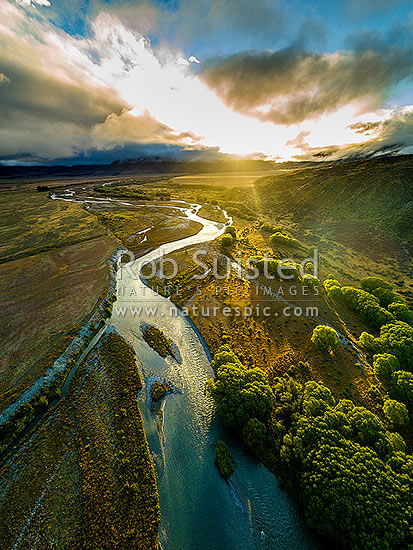 Ahuriri River, high country braided river, at sunset, looking upstream towards the Ahuriri Valley. Aerial view, Omarama, Waitaki District, Canterbury Region, New Zealand (NZ) stock photo.