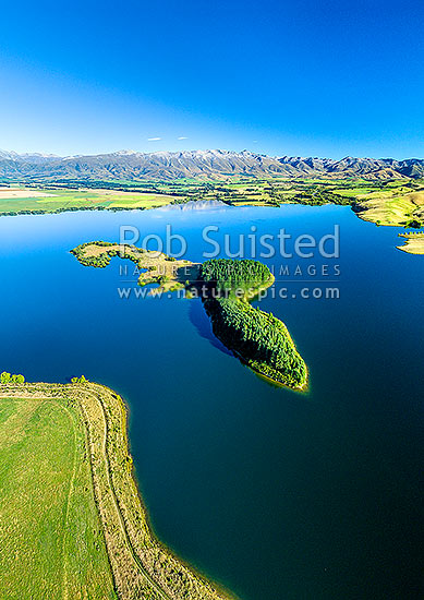 Lake Opuha and island, a man made lake for irrigation and power generation, with Sherwood Range beyond lush green farmland around Ashwick Flat. Aerial view, Fairlie, MacKenzie District, Canterbury Region, New Zealand (NZ) stock photo.