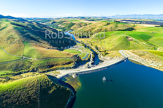 Lake Opuha and Opuha Dam, a man made lake for irrigation and power generation, looking downstream towards South Canterbury. Aerial view, Fairlie, MacKenzie District, Canterbury Region, New Zealand (NZ) stock photo.