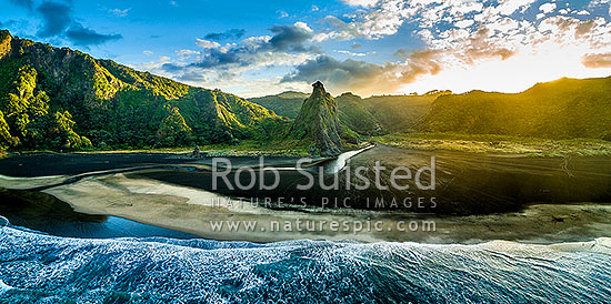 Karekare Beach at dawn, with The Watchman rock and Karekare Stream centre. Waitakere Ranges behind. Moody aerial panorama, Karekare Beach, Waitakere City District, Auckland Region, New Zealand (NZ) stock photo.