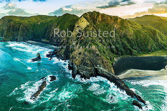 Farley Point and Union Bay (right) at Karekare beach. Looking north to Mercer Bay. Waitakere Ranges behind. Aerial view at dawn, Karekare Beach, Waitakere City District, Auckland Region, New Zealand (NZ) stock photo.