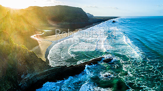 Karekare Beach, Union Bay and Panatahi Island, see from above Farley Point at sunrise. Aerial panorama, Karekare Beach, Waitakere City District, Auckland Region, New Zealand (NZ) stock photo.