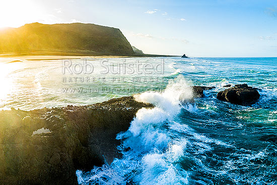 Karekare Beach, with waves crashing on Farley Point reef, with Panatahi Island beyond, at sunrise, Karekare Beach, Waitakere City District, Auckland Region, New Zealand (NZ) stock photo.