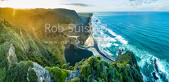 Karekare Beach, Union Bay, and Karekare Stream at sunset, looking south past Panatahi Island towards Whatipu. Aerial panorama from Farley Point. West Auckland, Waitakere Ranges, Karekare Beach, Waitakere City District, Auckland Region, New Zealand (NZ) stock photo.