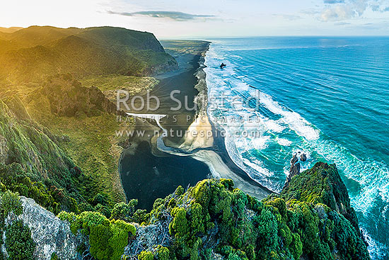 Karekare Beach, Union Bay, and Karekare Stream at sunset, looking south past Panatahi Island towards Whatipu. Aerial view from Farley Point. West Auckland, Waitakere Ranges, Karekare Beach, Waitakere City District, Auckland Region, New Zealand (NZ) stock photo.