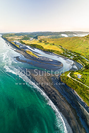 Awakino River mouth looking north at dawn. Aerial view with State Highway 3 (SH3) behind, Awakino, Waitomo District, Waikato Region, New Zealand (NZ) stock photo.