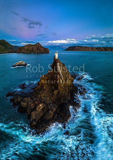 Whatipu Beach and Manukau Harbour entrance made safe by the Ninepin Rock lighthouse beacon. Paratutae Island beyond and South Head at right. Moody twilight aerial view, Whatipu Beach, Waitakere City District, Auckland Region, New Zealand (NZ) stock photo.