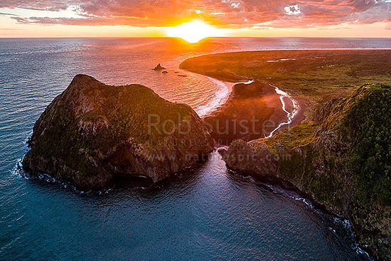 Whatipu Beach sunset behind Paratutae Island (left) and Ninepin Rock.  Burnett Head and Wing Head at right. Aerial view, Whatipu Beach, Waitakere City District, Auckland Region, New Zealand (NZ) stock photo.