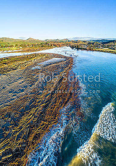 Tolaga Bay floods in June 2018 brought large amounts of forestry timber slash down rivers, covering beaches in timber and large volumes fo sediment into the marine environment. Tolaga Bay town behind. Aerial view, Tolaga Bay, Gisborne District, Gisborne Region, New Zealand (NZ) stock photo.