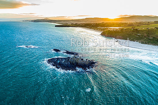 Dunedin South Coast, looking past Bird Island towards St Kilda Beach (left), Lawyers Head, Tomahawk Beach and Smaills Beach (right). Aerial view at sunset, Otago Peninsula, Dunedin City District, Otago Region, New Zealand (NZ) stock photo.