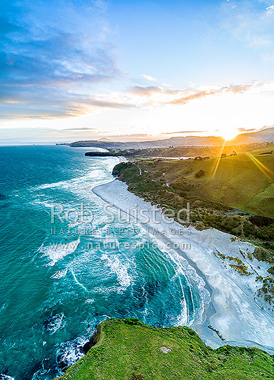 Dunedin South Coast, looking along Smaills Beach to Tomahawk Beach, Lawyers Head and St Kilda behind. Aerial view at sunset, from near Maori Head, Otago Peninsula, Dunedin City District, Otago Region, New Zealand (NZ) stock photo.