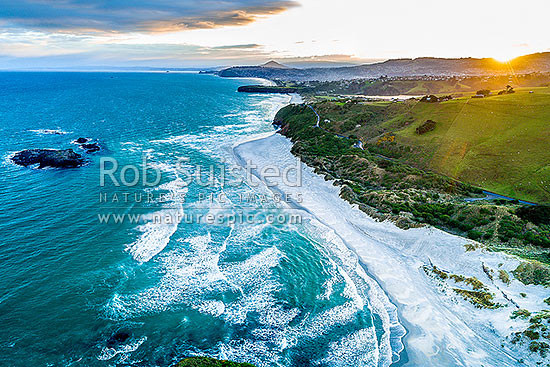 Smaills Beach and Dunedin South Coast, looking past Bird Island, past Tomahawk Beach and Lawyers Head toward St Kilda. Aerial view, Otago Peninsula, Dunedin City District, Otago Region, New Zealand (NZ) stock photo.