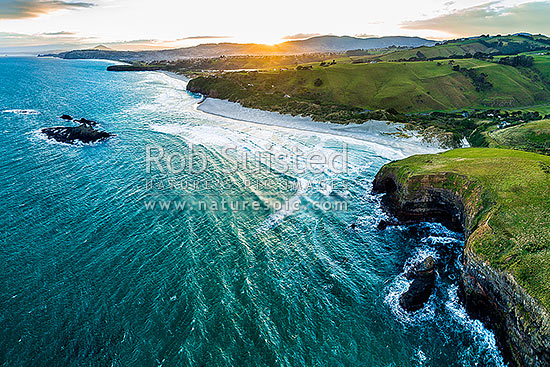 Dunedin South Coast, looking along Smaills Beach to Tomahawk Beach, Lawyers Head and St Kilda behind. Bird Island at left. Aerial view at sunset, from near Maori Head, Otago Peninsula, Dunedin City District, Otago Region, New Zealand (NZ) stock photo.