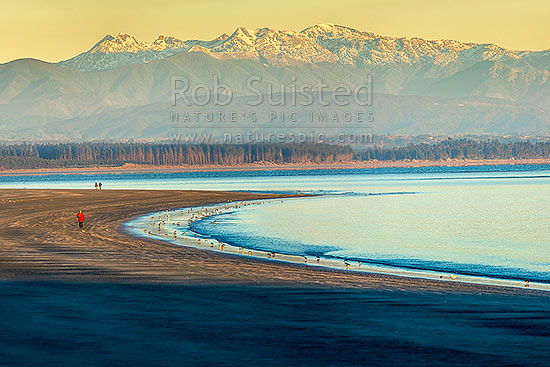 Tahunanui Beach in Tasman Bay. Rabbit Island and the Arthur Range in Kahurangi National Park beyond. Winter early morning with walkers and birds, Nelson, Nelson City District, Nelson Region, New Zealand (NZ) stock photo.
