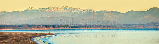 Tahunanui Beach in Tasman Bay. Rabbit Island and the Arthur Range in Kahurangi National Park beyond. Winter early morning with walkers and birds. Panorama, Nelson, Nelson City District, Nelson Region, New Zealand (NZ) stock photo.