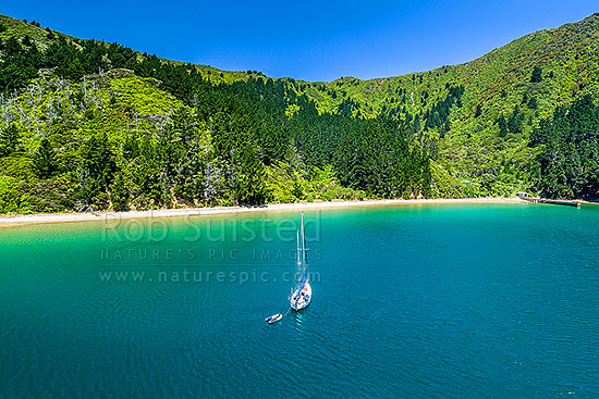 Wharehunga Bay and Wharehunga Beach, historical site from Captain Cook's visits. Aerial view in Queen Charlotte Sound, with visiting yacht in bay, Arapawa Island, Marlborough Sounds, Marlborough District, Marlborough Region, New Zealand (NZ) stock photo.