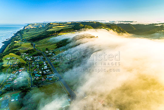 Mokau township with cold air intrusion flowing downslope towards the coast with a temperature inversion as the day warms at sunrise. Aerial view over misty morning. Looking north up Taranaki coast, Mokau, Waitomo District, Waikato Region, New Zealand (NZ) stock photo.