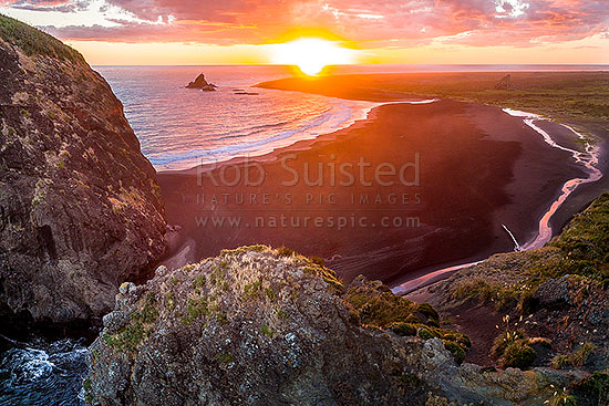 Whatipu Beach sunset beyond Paratutae Island and Ninepin Rock (left). Burnett Head below, Cutter Rock at right. Aerial view, Whatipu Beach, Waitakere City District, Auckland Region, New Zealand (NZ) stock photo.