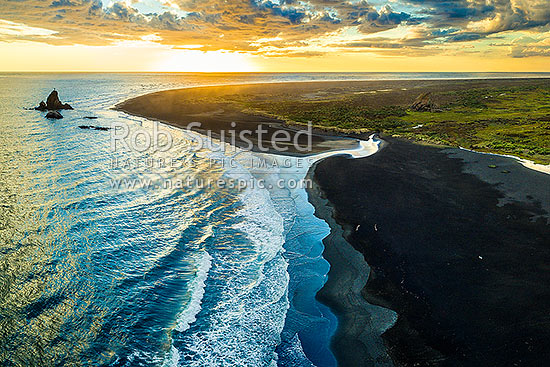 Whatipu Beach sunset over black ironsands.  Ninepin Rock at left, Amphlett Stream right. Aerial view, Whatipu Beach, Waitakere City District, Auckland Region, New Zealand (NZ) stock photo.