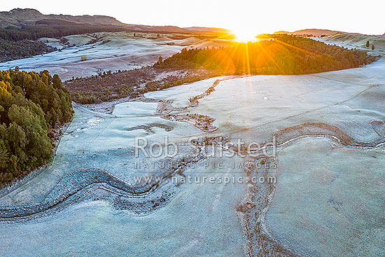 Balls Clearing Scenic Reserve and Clifton Conservation Area at dawn with heavy frost, as sun rises over hill. Headwaters of Mangatutu Stream. Aerial view, Puketitiri, Hastings District, Hawke's Bay Region, New Zealand (NZ) stock photo.