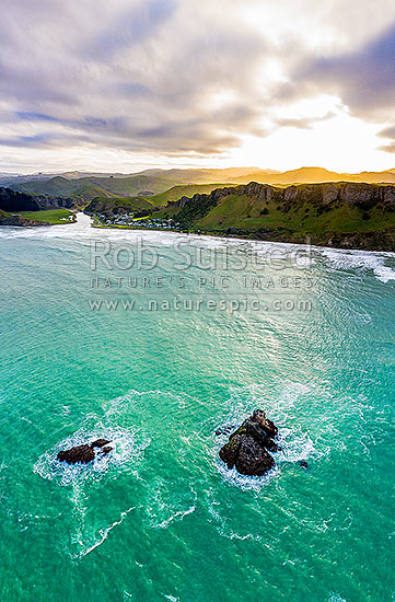 Kairakau Beach village on the Mangakuri River mouth at sunset with Hinemahanga Rocks in foreground. Aerial view, Kairakau Beach, Hawke's Bay Region, New Zealand (NZ) stock photo.