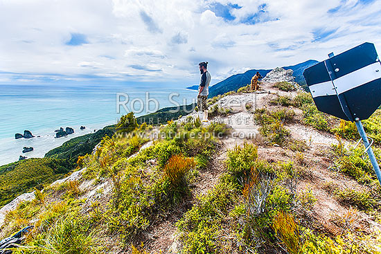 Mt George walkway (320m) above the Rapahoe Coast and Motukiekie Rocks. Walkway visitor at summit trig station, with spectacular views towards Punakaiki. Paparoa Range, Rapahoe, Grey District, West Coast Region, New Zealand (NZ) stock photo.