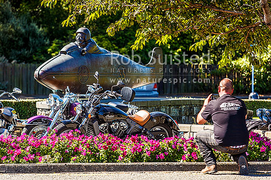 Gareth Pritchard of Kaiapoi pays homage at Burt Munro's and his Indian motorbike statue during Burt Munro Challenge week, by photographing his own modern day Indian Scout bike, Invercargill, Invercargill District, Southland Region, New Zealand (NZ) stock photo.