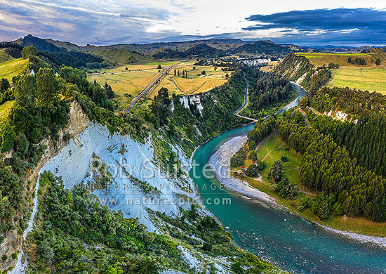 Rangitikei River and 100m high sandstone cliffs with rural farmland and Mangaweka township beyond. Mangarere Road centre, Pouwhakarua Conservation Area below. Aerial view, Mangaweka, Manawatu District, Manawatu-Wanganui Region, New Zealand (NZ) stock photo.
