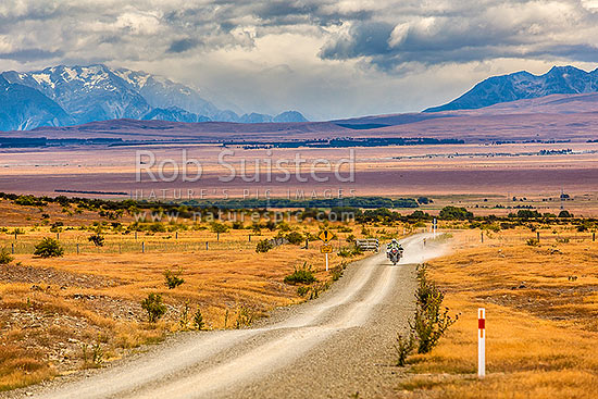MacKenzie Basin high country, looking from near Hakataramea Pass to Souithern Alps. Adventure touring motorcycle travelling back road, Hakataramea, MacKenzie District, Canterbury Region, New Zealand (NZ) stock photo.