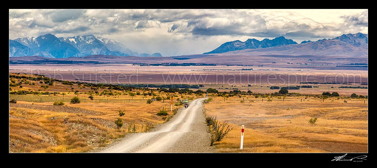 Image of MacKenzie Basin high country, looking from near Hakataramea Pass to Souithern Alps. Adventure touring motorcycle travelling back road. Panorama, Hakataramea, MacKenzie District, Canterbury Region, New Zealand (NZ) stock photo image