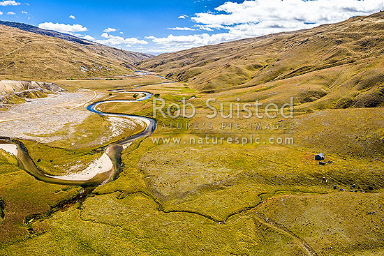 Nevis River valley near Whittens Stream looking north. Historic gold mining sluicings far left, old musterers hut at right. Garvie Mountains at right. Aerial view, Nevis, Central Otago District, Otago Region, New Zealand (NZ) stock photo.