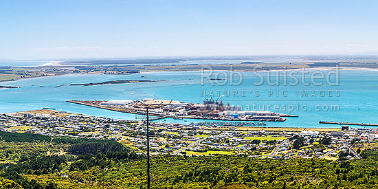 Bluff Harbour with Bluff Port and township, viewed from Bluff Hill. Oreti Beach and New River Estuary distant left, Invercargill City distant right. Panorama, Bluff, Invercargill District, Southland Region, New Zealand (NZ) stock photo.