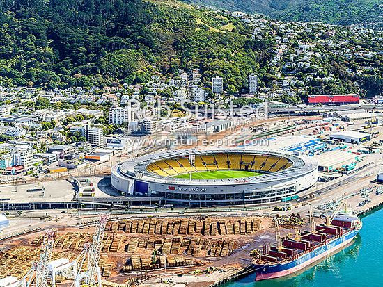 Westpac Stadium on the Wellington Thorndon waterfront, with log exports being loaded into bulk carrier ship from wharves below. Aerial view, Wellington, Wellington City District, Wellington Region, New Zealand (NZ) stock photo.