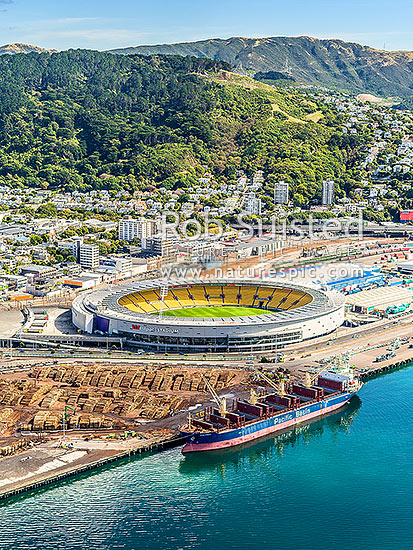Thorndon, with Westpac Stadium on the Wellington, with log exports being loaded into bulk carrier ship from wharves below. Tinakori Hill beyond, Wellington, Wellington City District, Wellington Region, New Zealand (NZ) stock photo.