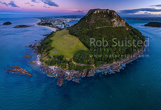 Mount Maunganui, or Mauao, at the Tauranga Harbour Entrance. 231m high lava dome. Moturiki and Motuotau Islands at left. Aerial view, Mount Maunganui, Tauranga District, Bay of Plenty Region, New Zealand (NZ) stock photo.