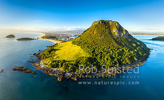 Mount Maunganui, or Mauao, at Tauranga Harbour Entrance. 231m high lava dome. Moturiki and Motuotau Islands at left. Aerial view, Mount Maunganui, Tauranga District, Bay of Plenty Region, New Zealand (NZ) stock photo.