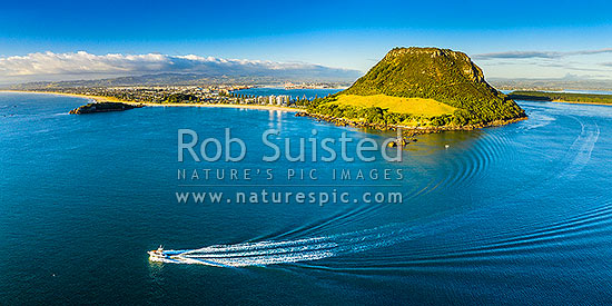 Mt Maunganui Mauao, a 231m lava dome at Tauranga Harbour entrance, with a big game fishing boat leaving harbour mouth. Aerial panorama, Mount Maunganui, Tauranga District, Bay of Plenty Region, New Zealand (NZ) stock photo.