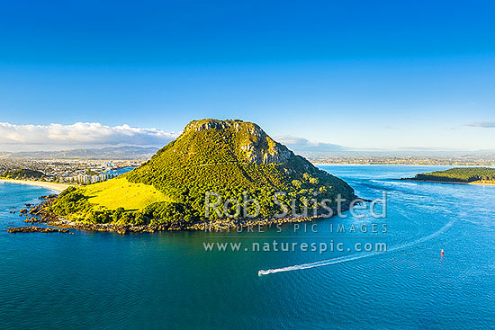 Mt Maunganui Mauao, a 231m lava dome at Tauranga Harbour entrance, with a small boat leaving harbour mouth. Tauranga Port and City beyond. Aerial view, Mount Maunganui, Tauranga District, Bay of Plenty Region, New Zealand (NZ) stock photo.