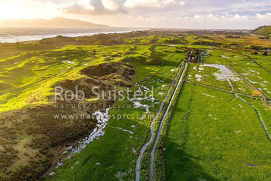 Whareroa River peatland and dunes, low lying and holding water after rain. Queen Elizabeth Regional Park, aerial view looking north. Kapiti Island behind, Paekakariki, Kapiti Coast District, Wellington Region, New Zealand (NZ) stock photo.