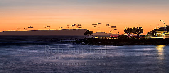 Plimmerton Beach sunset, looking towards Mana Island, with traffic moving on Sunset Parade at dusk. Panorama, Plimmerton, Porirua City District, Wellington Region, New Zealand (NZ) stock photo.