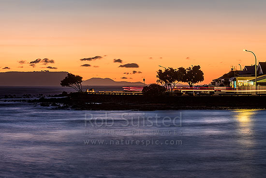 Plimmerton Beach sunset, with traffic moving on Sunset Parade at dusk. Mana Island behind at left, Plimmerton, Porirua City District, Wellington Region, New Zealand (NZ) stock photo.