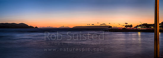 Plimmerton Beach sunset. Titahi Bay coast at left, Mana Island centre right, and South Island in distance. Panorama, Plimmerton, Porirua City District, Wellington Region, New Zealand (NZ) stock photo.