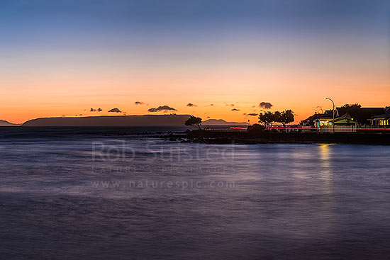 Plimmerton Beach sunset with traffic and vehicle lights passing on Sunset Parade road. Mana Island left and South Island in distance, Plimmerton, Porirua City District, Wellington Region, New Zealand (NZ) stock photo.
