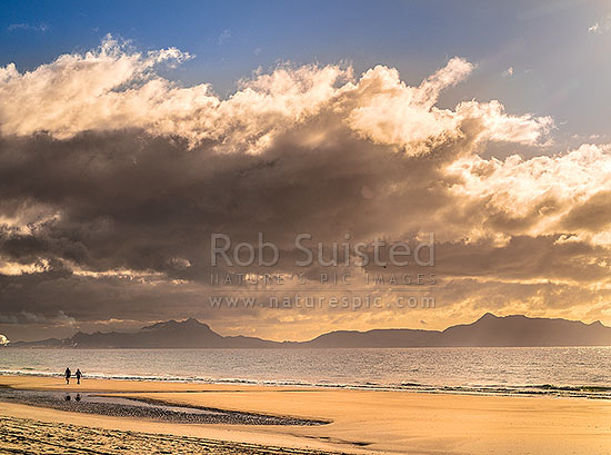 Ruakaka Beach, with a couple of people walking in evening light. Marsden Pont and Mt Manaia (420m) at the Whangarei Harbour Heads & Bream Head, Ruakaka, Whangarei District, Northland Region, New Zealand (NZ) stock photo.