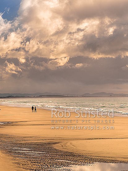Ruakaka Beach panorama, with people walking in evening light. Mt Manaia (right, 420m) behind right, at the Whangarei Harbour Heads, Ruakaka, Whangarei District, Northland Region, New Zealand (NZ) stock photo.