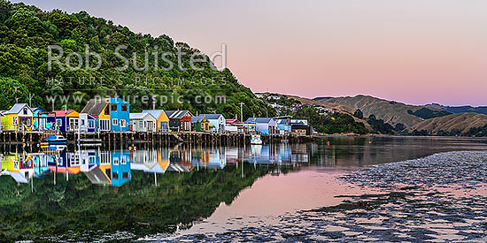 Boatsheds at Mana on the Pauatahanui Arm Inlet of the Porirua Harbour, with boats on moorings. Evening twilight. Panorama, Paremata, Porirua City District, Wellington Region, New Zealand (NZ) stock photo.