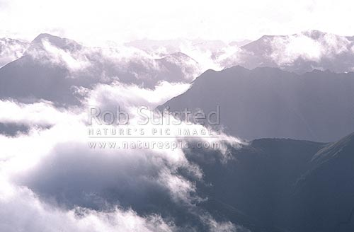 Clouds hanging over valleys of the Southern Alps, Arthur's Pass National Park, Selwyn District, Canterbury Region, New Zealand (NZ) stock photo.