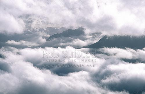 Clouds hanging over mountain valleys, Arthur's Pass National Park, Selwyn District, Canterbury Region, New Zealand (NZ) stock photo.