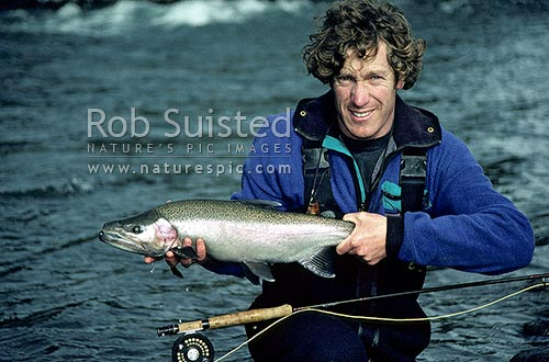Fisherman with Rainbow trout - Tongariro River - Silly Pool, Turangi, Taupo District, Waikato Region, New Zealand (NZ) stock photo.